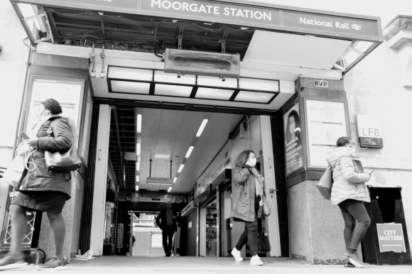 Black & White: a view into the station entrance on the north side of Moorgate looking through to Moorfields. Two passengers walking through and two pedestrians walking by