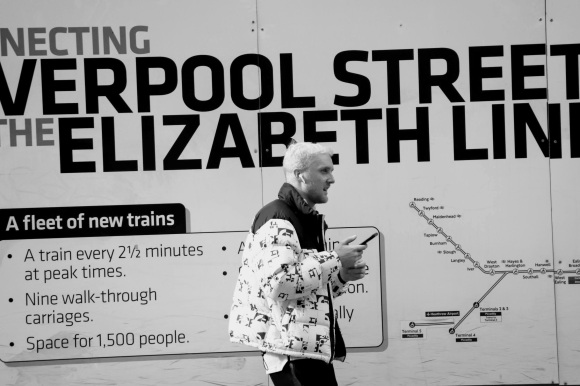 Black & White: building hoarding disaplaying part o 'connecting Liverpool Street - The Elizabeth Line. Standing in front is a blond haired young gent talking on his mobile phone looking to the right. He's wearing a predominantly white puffer jacket with black lettering.