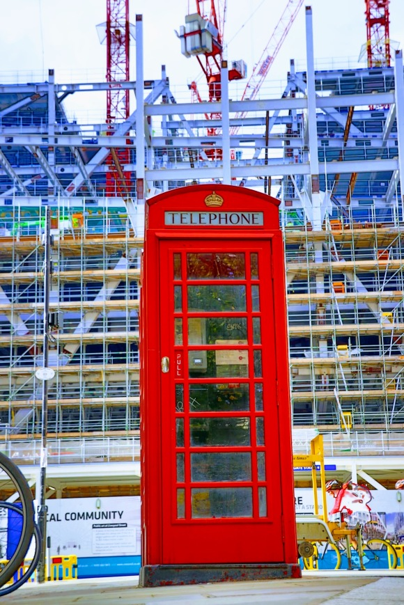 Colour: a ground shot looking up at a red telephone box in the foreground. A scafolding covered building in the background