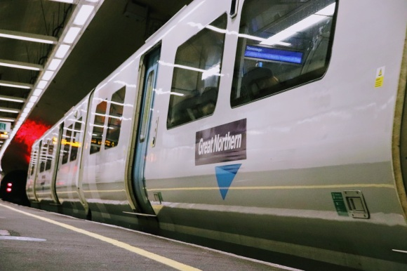 Colour: A train departing platform 9 emblazened with 'Great Northern' as part of its livery