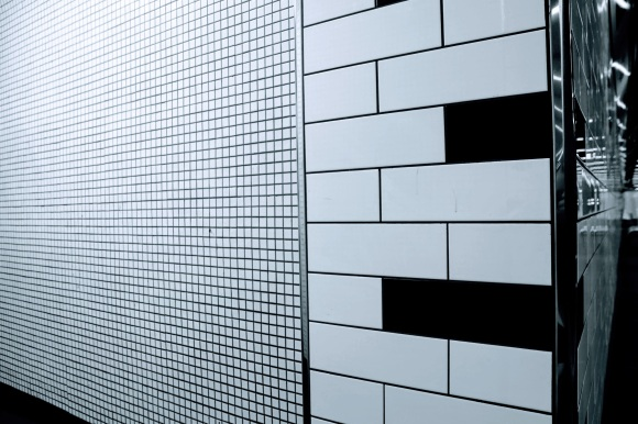 Black & White: a tiled wall of two trypes: small white squares and oblong black and white tiles