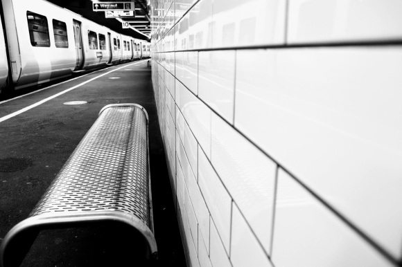 Black & White: looking down platform 10 with three parallel views: from left to right - train standing on the platform; perforated metal seat, and a white tiled wall