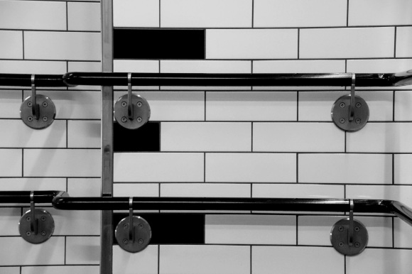 Black & White: black and white wall tiles running in parallel with two lines of black hand rails