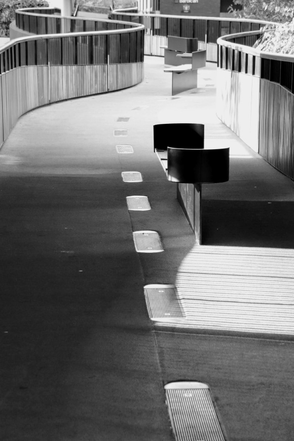 Black and White: an 'S'' curved high level walkway with sides crafted out of two different wood colours. A bench in the foreground with curved ends, and the centre of the floor inlaid with ovoid grills. Sun shining from the left casting shadows