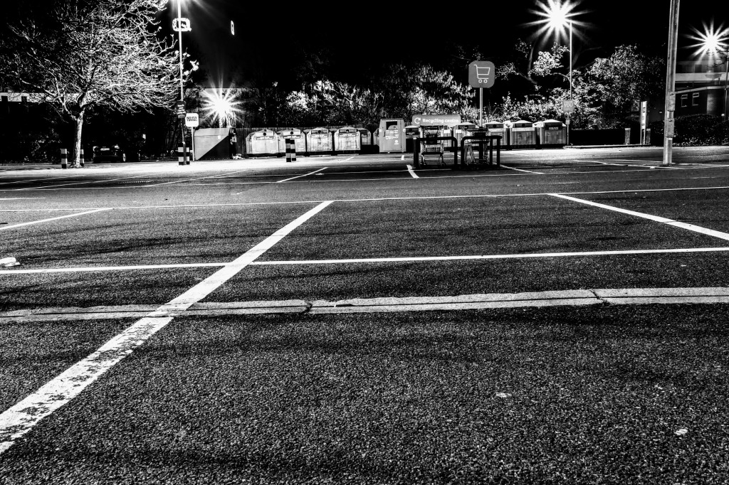 an empty car park with recycling bins in the distance
