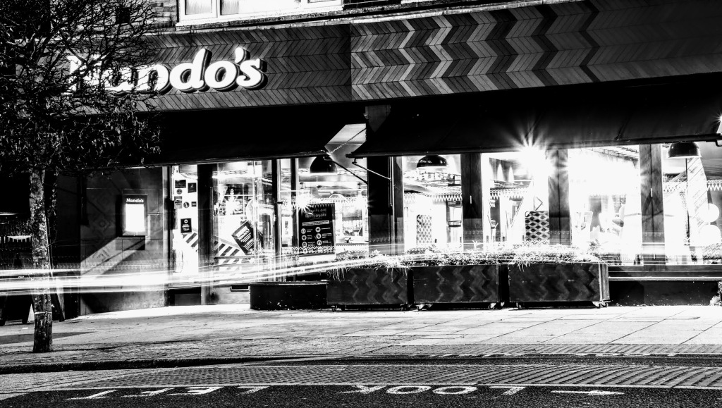 A black and white view of the front of Nando's with their shop windows all lit up