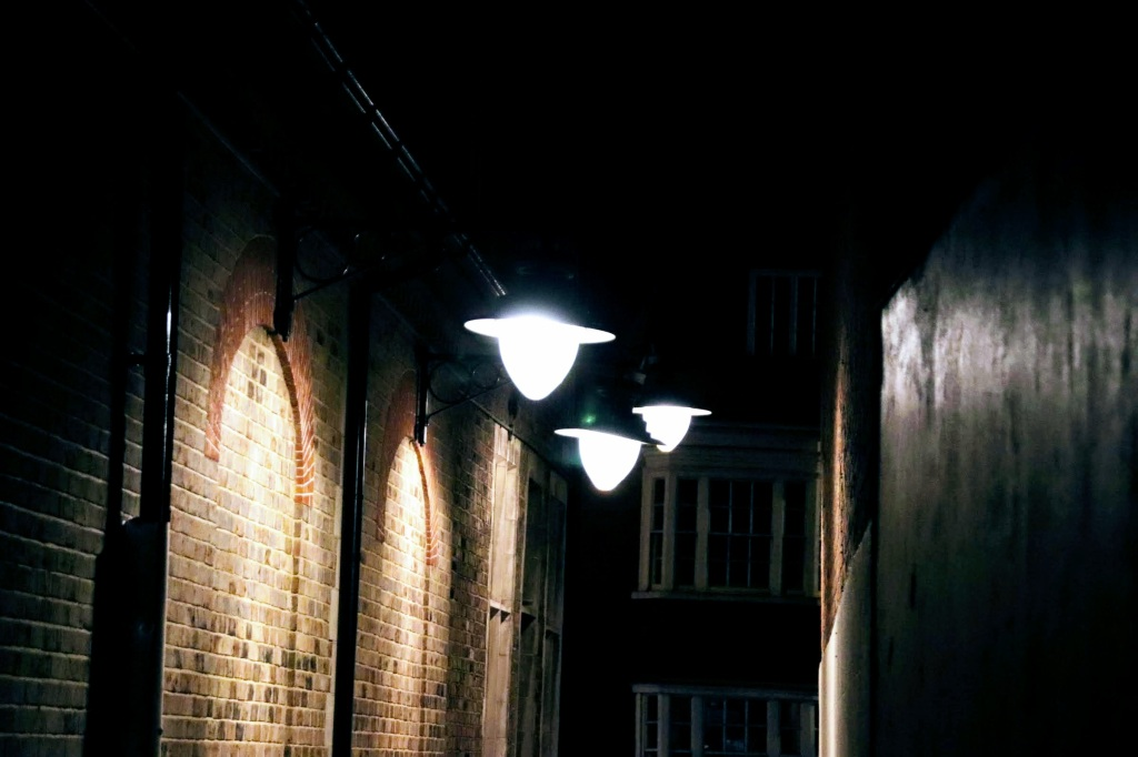 three victorin style street lights shining on a brick wall